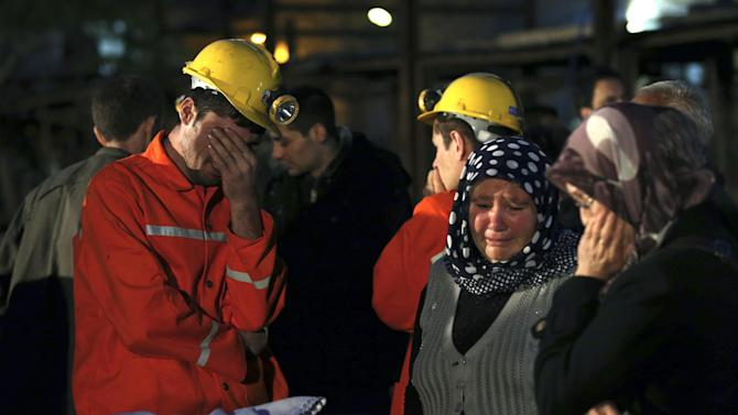 Miners and family members wait outside a coal mine following an explosion in Soma, western Turkey, early Wednesday, May 14, 2014. Rescuers desperately raced against time to reach more than 200 miners trapped underground Wednesday after an explosion and fire at the coal mine in western Turkey killed over 200 workers, authorities said, in one of the worst mining disasters in Turkish history. (AP Photo/Emrah Gurel)
