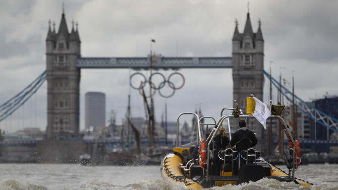 In this photo taken Wednesday, July 4, 2012, a high-speed 12-seater rigid inflatable boat, run by the Protection Services International company, travels towards Tower Bridge over London's river Thames, adorned with a huge Olympic rings to honor the games that will take place from July 27-Aug. 12. Companies like Protection Services International are just one of the many catering to the super rich who are coming to the London games and demand top security and easy transport. (AP Photo/Lefteris Pitarakis)
