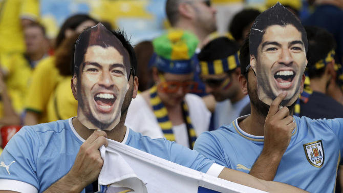 Uruguay fans wear masks of Uruguay's Luis Suarez before the World Cup round of 16 soccer match between Colombia and Uruguay at the Maracana Stadium in Rio de Janeiro, Brazil, Saturday, June 28, 2014. (AP Photo/Marcio Jose Sanchez)
