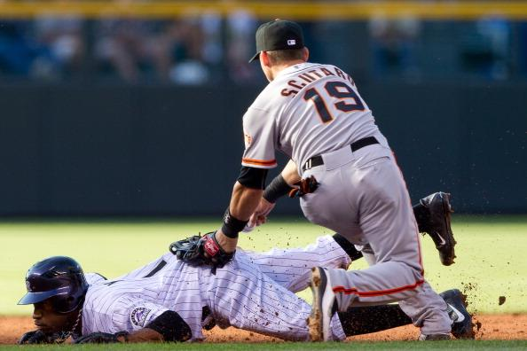 Eric Young Jr. #1 of the Colorado Rockies dives to avoid a tag by Marco Scutaro #19 of the San Francisco Giants as he gets caught in a pickle during the first inning at Coors Field on August 4, 2012 in Denver, Colorado. Young Jr. was later tagged out. (Photo by Justin Edmonds/Getty Images)