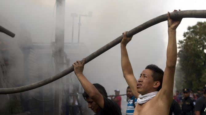 Vendors hold hoses as they help firefighters control a fire in a tire warehouse in La Terminal, the largest and most important market in Guatemala City, Wednesday, May 6, 2015. According to the fire department, firefighters worked for two hours to control the fire that affected several shops. No injuries where reported. (AP Photo/Moises Castillo)