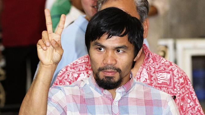 FILE - In this June 16, 2012, file photo, former welterweight world champion Manny Pacquiao flashes the sign of peace during a Mass in Manila, Philippines. Champion boxers Floyd Mayweather Jr. and Pacquiao have reached a confidential settlement Tuesday, Sept. 25, 2012, in their federal defamation case in Las Vegas. Attorneys for all sides say the terms won't be disclosed. (AP Photo/Pat Roque, file)