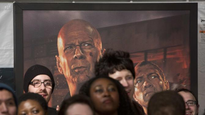 """A poster featuring cast members Bruce Willis and Jai Courtney hangs behind a crowd as the actors met with fans to celebrate the opening of their new film """"A Good Day To Die Hard"""" in New York"""