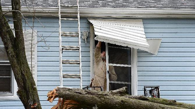 Harold Grant tries to repair his front door awning before cutting up a tree that broke in his front yard  after a tornado touched down, damaging 25 homes and knocking out power Wednesday, Jan. 30, 2013, in Ashland City, Tenn. Around 25 homes in Ashland City had minor damage. (AP Photo/Mark Zaleski)