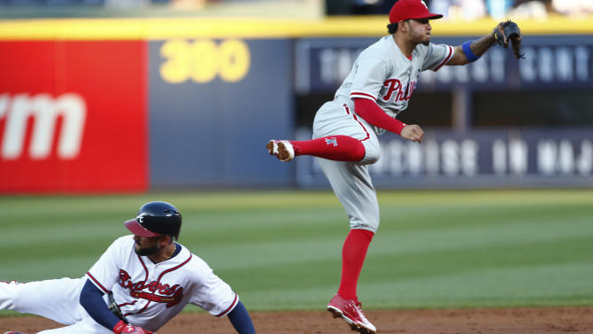 Philadelphia Phillies shortstop Freddy Galvis avoids Atlanta Braves right fielder Nick Markakis  as he turns a double play on an Andrelton Simmons ground ball in the first inning of a baseball game  Monday, May 4, 2015, in Atlanta.  (AP Photo/John Bazemore)