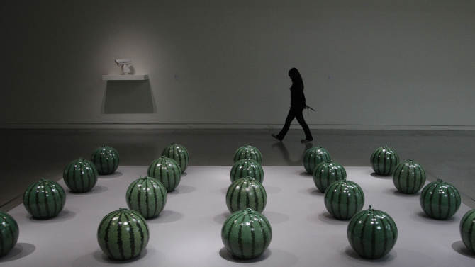 """A visitor passes an instillation entitled """"Watermelon"""" by the Chinese artist and activist Ai Weiwei at the """"Ai Weiwei is Absent"""" exhibition in the Taipei Fine Arts Museum in Taipei, Taiwan, Friday, Oct. 28, 2011. The exhibition opens Oct. 29 and will run for three months. (AP Photo/Wally Santana)"""