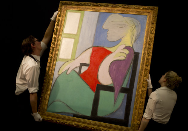 "Two Sotheby's employees adjust a painting by Pablo Picasso entitled ""Femme assise pres d'une fenetre"" 1932, at Sotheby's auction house during a press preview in London, Thursday, Jan. 31, 2013. The work is estimated to sell for some 25-35 million pounds (US$ 39.5-55 million, euro 29.1-40.8 million) when sold at auction on Feb. 5, in London. (AP Photo/Alastair Grant)"