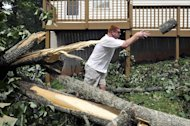 Gary Davis tosses aside a section of a Tulip Poplar tree the fell behind a friend's house on Greenwood Drive in Lynchburg, Va., July 1, 2012. The tree fell between two houses, narrowly sparing both. (AP Photo/The News & Advance, Parker Michels-Boyce)