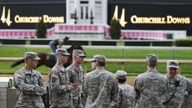 Military personnel stand by the race track during morning workouts at Churchill Downs Friday, May 3, 2013, in Louisville, Ky. Security has been stepped up at the track for the running of the 139th Kentucky Oaks and Kentucky Derby. (AP Photo/David Goldman)