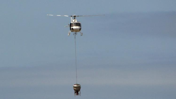 In this Nov. 11, 2012 photo released by Galapagos National Park, a helicopter tests carrying a container that will hold poisonous bait to kill rats on the Galapagos Islands, over Baltra Island. To preserve the unique birds, reptiles and native plants that make the Galapagos Islands such an ecological treasure, authorities will start on Wednesday, Nov. 14, 2012 phase II of a mass kill-off of black and Norway rats, an invasive species introduced to the Pacific Ocean islands by whalers and buccaneers beginning in the 17 century. (AP Photo/Galapagos National Park)