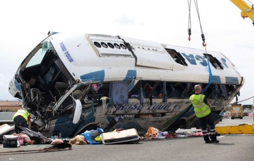 <p>Workers tow a bus out of the road after it crashed along the A8 highway, carrying about fifty Romanian nationals on September 2, in the southern French city of Vidauban. The bus from Spain blew a tyre and overturned, killing an infant and injuring about 35 people, some critically, local officials said.</p>