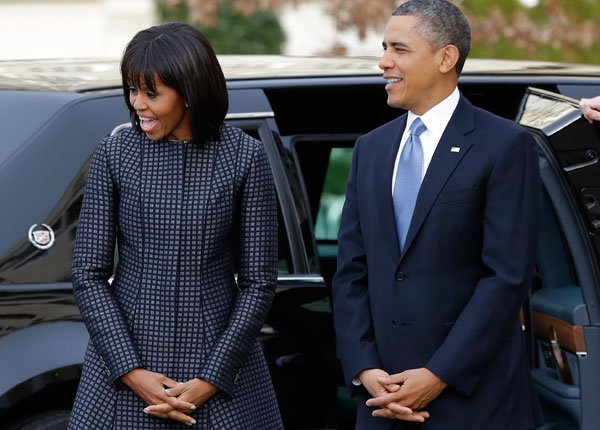 President Barack Obama and first lady Michelle Obama react as they watch their daughters as the first family arrives at St. John's Church in Washington, Monday, Jan. 21, 2013, for a church service dur