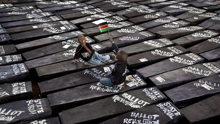 "Children of one of the protest organizers lie in the shade on top of mock coffins, on which are written ""State Burial, Ballot Revolution"", before demonstrators carried the coffins to the Parliament and burned them, in Nairobi, Kenya Wednesday, Jan. 16, 2013. Hundreds of demonstrators angered at outgoing Kenyan legislators, whose term ended earlier this week and who earn about $175,000 a year in a country where the average annual income is $1,700, doused 221 mock coffins with gasoline, one for each legislator, to protest against last week's attempt to award themselves a $110,000 bonus, which was vetoed by the president. (AP Photo/Ben Curtis)"