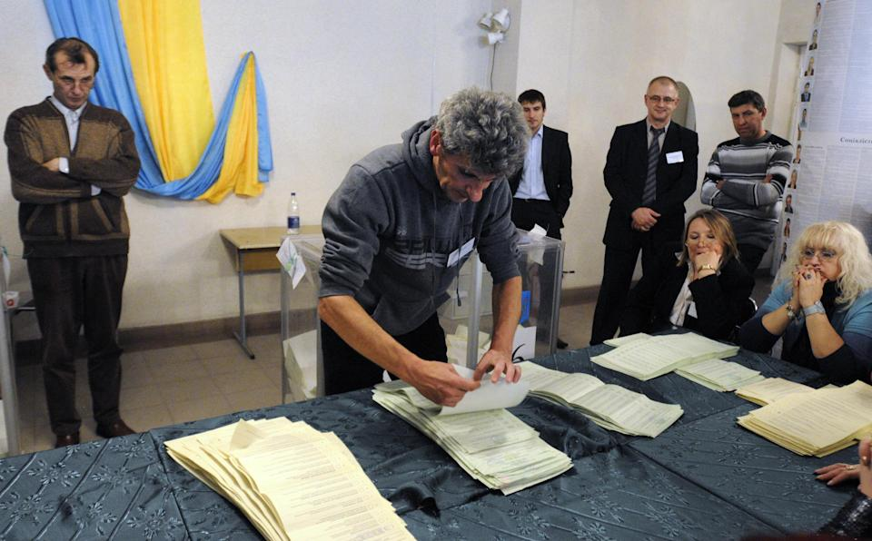Election commission officials count ballots at a polling station in Kiev, Ukraine, Sunday, Oct. 28, 2012. Ukrainians are electing a parliament on Sunday in a crucial vote tainted by the jailing of top opposition leader Yulia Tymoshenko and fears of election fraud. (AP Photo/Sergei Chuzavkov)