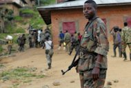 "A soldier from the mutinous 8th Military Region of the DR Congo army stands guard as his fellow renegades head for their camp in Kanyabayonga, in Eastern DRC. The United States is suspending military aid to Rwanda because of ""deep concerns"" over evidence it is supporting the mutiny in DR Congo."