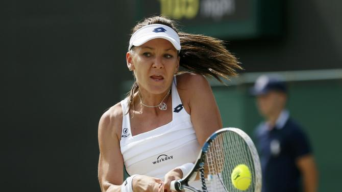 Agnieszka Radwanska of Poland hits a shot during her match against Jelena Jankovic of Serbia at the Wimbledon Tennis Championships in London