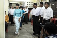 Aung San Suu Kyi (left) arrives at National League for Democracy headquarters in Yangon to attend a meeting. The party announced Sunday it will postpone its parliamentary debut, in the first sign of discord between Myanmar's newly-elected opposition and reformist government