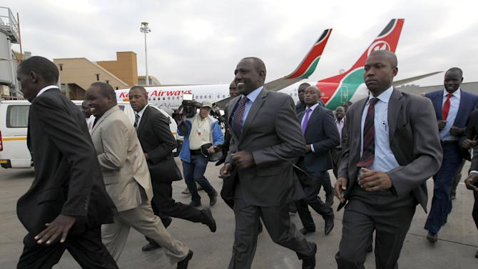 Kenya's Deputy President Ruto runs to receive the national athletics team at the Jomo Kenyatta airport Nairobi