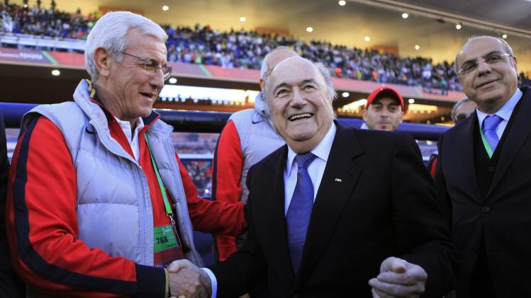 FIFA President Blatter shakes hands with Lippi, coach of China's Guangzhou Evergrande, before their 2013 FIFA Club World Cup third place soccer match against Brazil's Atletico Mineiro in Marrakech stadium