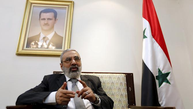 Syrian Information Minister Omran al-Zoubi speaks during an interview with Reuters at his office in Damascus, Syria