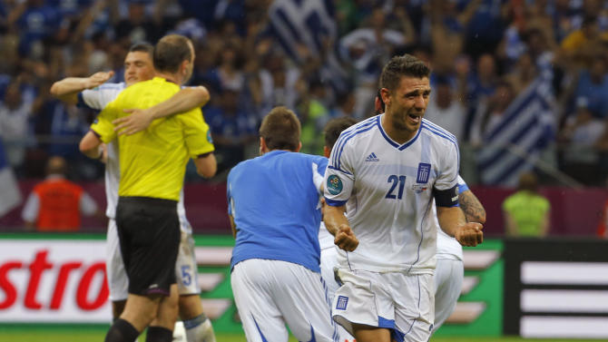 Greece's Costas Katsouranis, right, and teammates celebrate their 1-0 win during the Euro 2012 soccer championship Group A  match between Greece and Russia in Warsaw, Poland, Saturday, June 16, 2012. (AP Photo/Sergey Ponomarev)