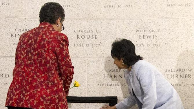 William Henderson Foote's great grand daughter Patricia Nolcox, right, and great grand niece Bettye Gardner, left, place flowers near the newly-unveiled on Bureau of Alcohol, Tobacco, Firearms and Explosives (ATF) Memorial Wall during a memorial ceremony to honor the first African American post-reconstruction era federal law enforcement officer killed in the line of duty, Monday, May 14, 2012, in Washington.  The name of William Henderson Foote, a deputy collector with an ATF legacy agency, the U.S. Department of the Treasury, Bureau of Internal Revenue (BIR), was unveiled on ATFís Memorial Wall during an event commemorating National Police Week. Foote was killed Dec. 29, 1883, in Yazoo City, Miss., almost 130 years ago.   (AP Photo/Manuel Balce Ceneta)