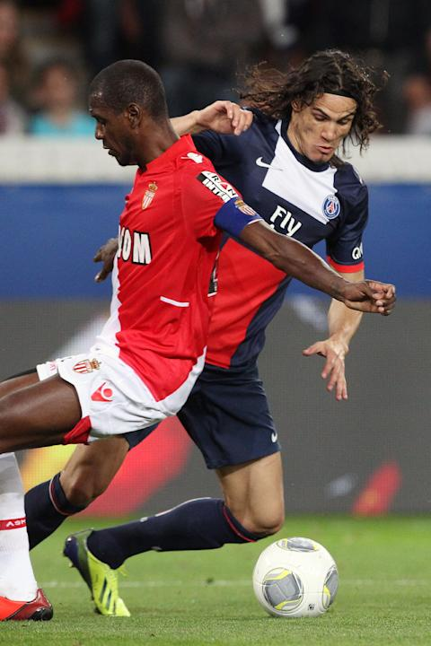 Paris Saint Germain's forward Edinson Cavani from Uruguay, right,  challenges for the ball with Monaco's defender Eric Abidal, during their French League One soccer match, at the Parc des Princes stad
