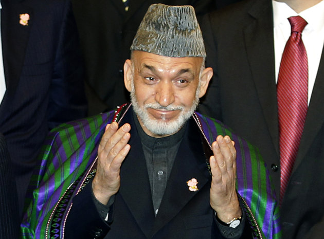 FILE - In this July 8, 2012 file photo, Afghan President Hamid Karzai gestures while posing for a group photo with participants of an international conference on Afghan civilian assistance, at a hotel in Tokyo. President Karzai said Monday, July 9, he is encouraged by pledges to provide Afghanistan with $16 billion in aid, but warned that corruption in his country cannot be rooted out unless donors themselves take more action. (AP Photo/Shizuo Kambayashi, File)