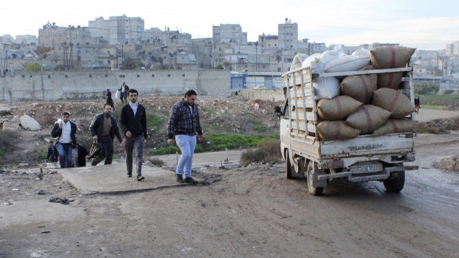 """In this photo taken on Wednesday Dec. 5, 2012, Syrian citizens cross from the area that controlled by the Syrian forces loyal to president Bashar Assad, to an area controlled by the Free Syrian Army, at the only crossing point between the two groups, in Aleppo, Syria. Syria blasted NATO's move to deploy Patriot missiles along its border with Turkey, calling the decision """"provocative,"""" as the West took a major step toward a possible military role in the civil war. (AP Photo/Abdullah al-Yassin)"""
