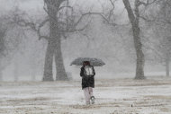 A woman walks through Central Riverside Park on a snowy Wednesday morning in Wichita, Kan., Feb. 20, 2013. Hundreds of snow plows and salt spreaders took to the highways of the nation&#39;s heartland Wednesday, preparing for a winter storm that could dump up to a foot of snow in some regions and bring dangerous freezing rain and sleet to others. (AP Photo/The Wichita Eagle, Jaime Green)