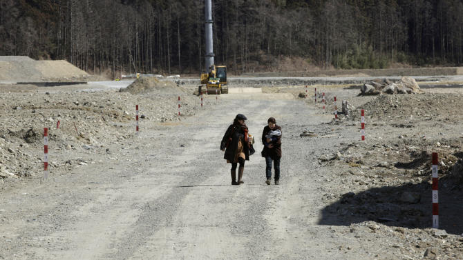 Women approach Okawa Elementary School where 74 of the 108 students went missing after the March 11 tsunami in Ishinomaki, Miyagi prefecture, Japan, Monday, March 11, 2013. The two-year anniversary Monday of Japan's devastating earthquake, tsunami and nuclear catastrophe is serving to spotlight the stakes of the country's struggles to clean up radiation, rebuild lost communities and determine new energy and economic strategies.  (AP Photo/Shizuo Kambayashi)