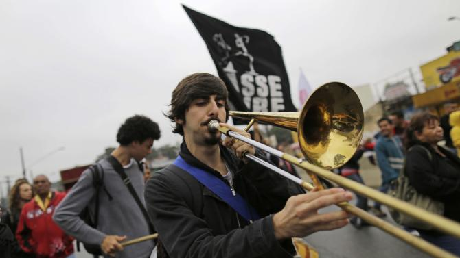 A man plays a trombone during a protest in the Capao Redondo neighborhood of Sao Paulo, Brazil, Tuesday, June 25, 2013. Protesters on Tuesday returned to the streets in low-income suburbs of Brazil's biggest city to demand better education, transport and health services, one day after President Dilma Rousseff proposed a wide range of actions to reform Brazil's political system and services. (AP Photo/Nelson Antoine)
