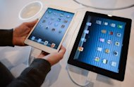 A customer compares an iPad mini (L) to an iPad at an Apple store in Rome. In tablets, Apple&#39;s market share has fallen to just over 50 percent from 65 percent in the second quarter as Android devices gain ground, according to IDC figures