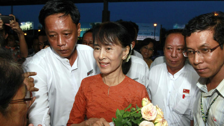 Myanmar opposition leader Aung San Suu Kyi, center, is greeted by a supporter upon her arrival at Yangon International Airport in Yangon, Myanmar, to leave for Bangkok, Thailand, on Tuesday, May 29, 2012. It is her first trip out of Myanmar in 24 years. (AP Photo/Khin Maung Win)