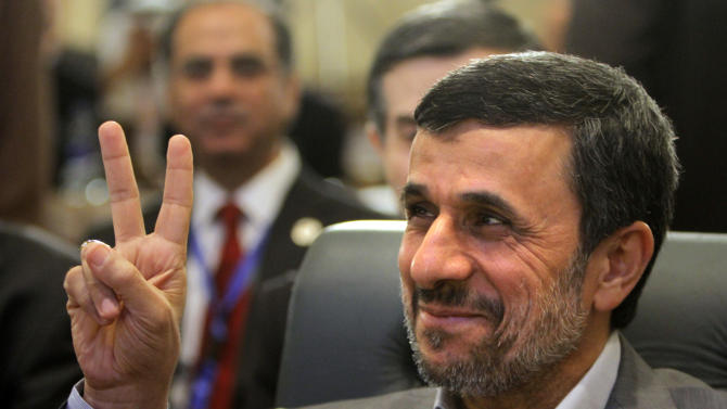 "Iran's President Mahmoud Ahmadinejad flashes the victory sign as he attends the 12th summit of the Organization of Islamic Cooperation in Cairo, Egypt, Wednesday, Feb. 6, 2013. Iran's president says his country is ready to provide a ""big credit line"" to help revive the distressed economy of Egypt, which saw its foreign currency reserves — already at critically low levels — fall nearly 10 per cent last month. (AP Photo/Amr Nabil)"