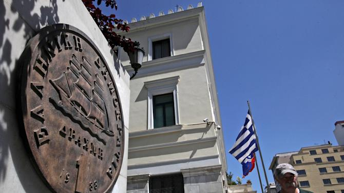 A man passes a plaque of a Greek one-drachma coin, which was replaced by the euro in 2002, in central Athens, on Tuesday, May 22, 2012. Greece gets underway for crucial June 17 elections with the vote seen as a choice on whether debt-stricken Greece stays in the euro.(AP Photo/Petros Giannakouris)