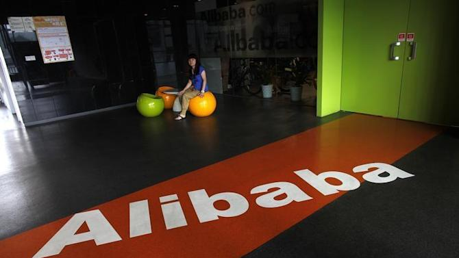 An employee sits next to a logo of Alibaba during a media tour organised by government officials at the company's headquarters on the outskirts of Hangzhou