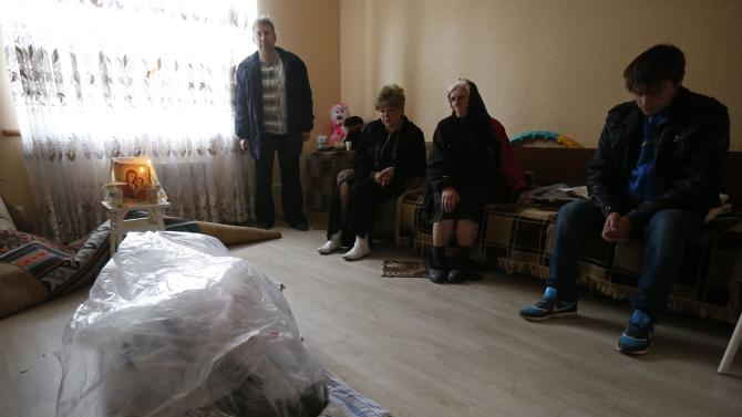 Relatives mourn next to the covered body of a  woman, whom they said was killed during a rocket shelling in Debaltseve