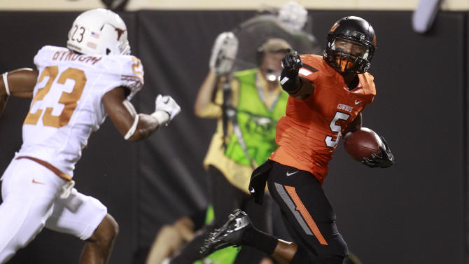 Oklahoma State wide receiver Josh Stewart (5) runs past Texas cornerback Carrington Byndom (23) for a touchdown in the first quarter of an NCAA college football game in Stillwater, Okla., Saturday, Sept. 29, 2012. (AP Photo/Sue Ogrocki)