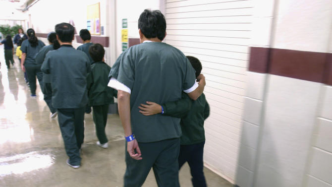 FILE - A Feb. 9, 2007 file photo provided by the Department of Homeland Security shows family detainees walking down the hall at the T. Don Hutto Residential Center in Taylor, Texas. The U.S. is locking up more illegal immigrants than ever before, generating a lucrative business for the nation's largest prison companies. (AP Photo/Department of Homeland Security, Charles Reed, HO, File)