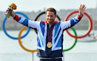 Britain&#39;s Ben Ainslie acknowledges the applause on the podium after receiving the gold medal in the Finn sailing class at the London 2012 Olympic Games, in Weymouth on August 5, 2012. Ainslie said on Tuesday that he may yet carry on to the 2016 Rio Olympics after all