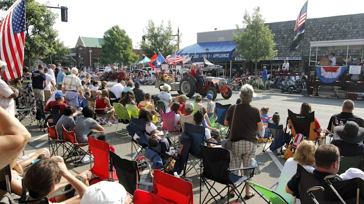 Spectators gather to watch the annual LibertyFest Fourth of July Parade in downtown Edmond, Okla, on Thursday, July 4, 2013. Authorities say a boy died after being run over by a float at the end of the parade. Edmond Police Officer James Hamm says the boy was riding on a float at the city's LibertyFest parade on Thursday. Hamm says the boy fell or got down from the float at the end of the parade and was struck by the same vehicle. (AP Photo/The Oklahoman, Paul Hellstern)