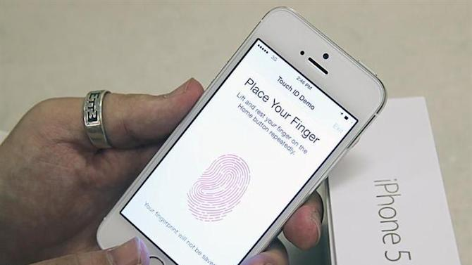 An employee tests the fingerprint scanner on the new Apple iPhone 5S at a Verizon store in Orem, Utah