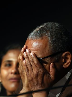 Director Abderrahmane Sissako holds his hands over his face while answering a question during a press conference for Timbuktu at the 67th international film festival, Cannes, southern France, Thursday, May 15, 2014. (AP Photo/Alastair Grant)
