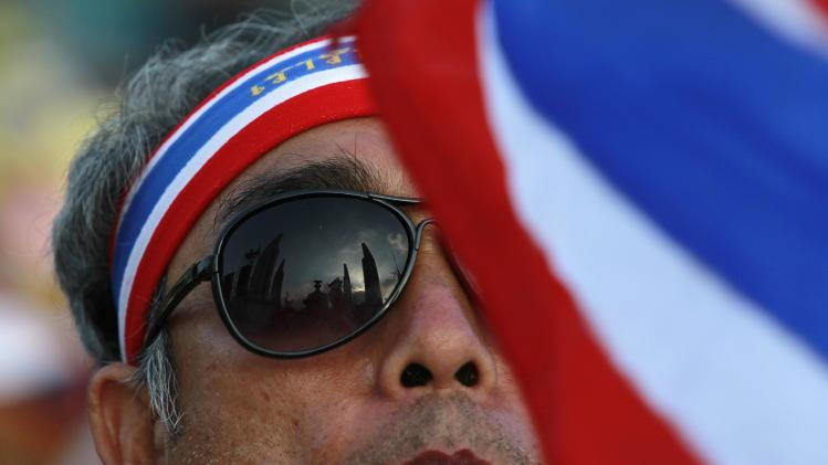 Democracy Monument is reflected in the sunglasses of an anti-government protester during a rally in central Bangkok