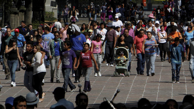 People enter the Chapultepec Park in Mexico City, Sunday, Nov. 18, 2012.  Chapultepec is  a park divided between shady stretches of forest and more-developed plazas, fountains and sculpture gardens. On weekends, the northern end is crammed with vendors, entertainers and families out for the day. (AP Photo/Marco Ugarte)