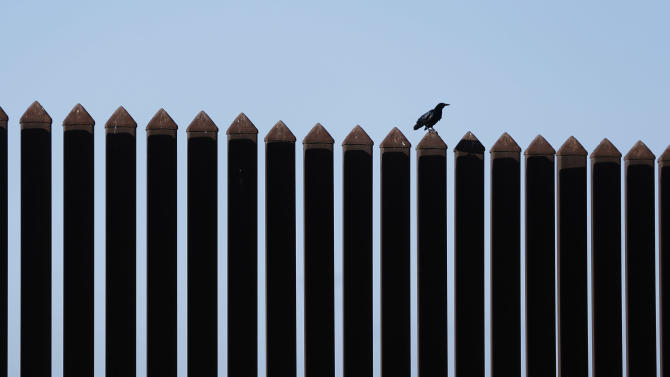 In this Sept. 4, 2012, photo, a bird perches on the U.S.-Mexico border fence that passes through the Nature Conservancy's southernmost preserve in Brownsville, Texas. Since 2008, hundreds of landowners on the border have sought fair prices for property that was condemned to make way for the fence, but many of them received initial offers that were far below market value. (AP Photo/Eric Gay)