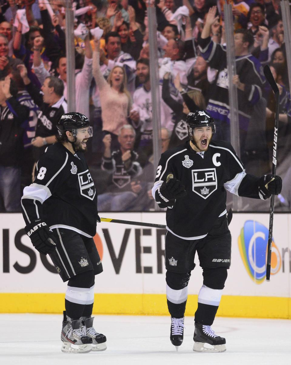 Los Angeles Kings right wing Dustin Brown (23) and Los Angeles Kings defenseman Drew Doughty (8) react after Brown scored his second goal of the first period against the New Jersey Devils during Game 6 of the NHL hockey Stanley Cup finals, Monday, June 11, 2012, in Los Angeles.  (AP Photo/Mark J. Terrill)
