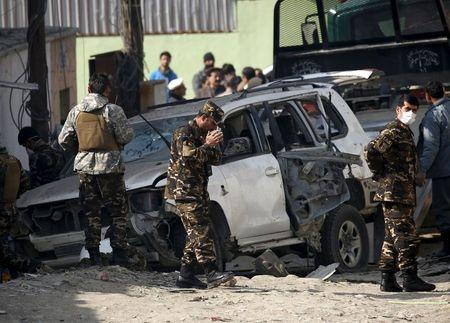 Afghan security personnel keep watch at the site of a suicide blast in Kabul