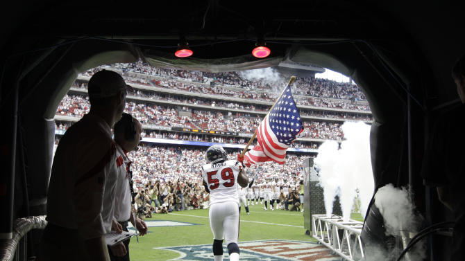 Houston Texans linebacker DeMeco Ryans (59) takes the field carrying a flag before an NFL football game against the Indianapolis Colts, Sunday, Sept. 11, 2011, in Houston. (AP Photo/David J. Phillip)